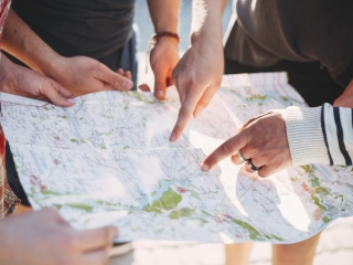 Traveling, sightseeing, group travel, city tour, student exchange program, vacation, holiday. Friends searching the location on map, planing journey